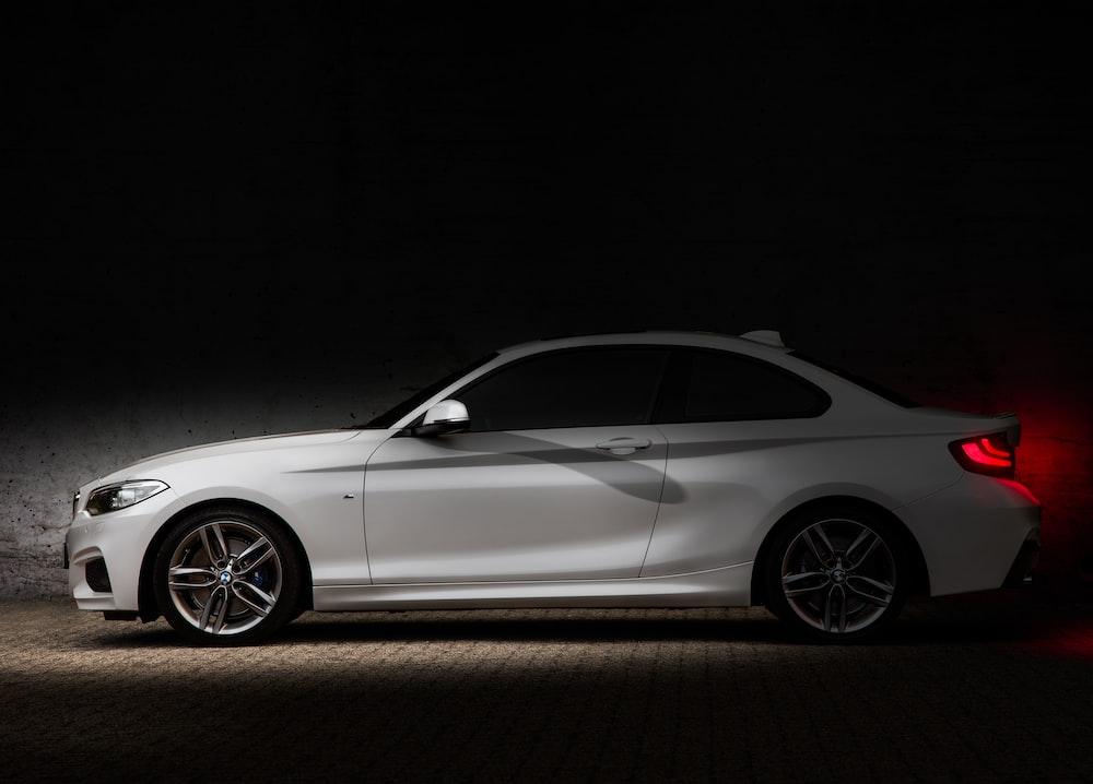 white coupe on black background
