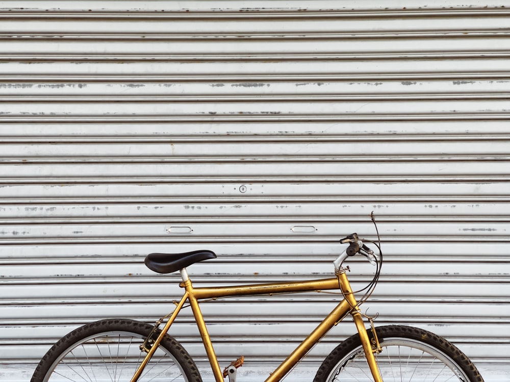 yellow and black bicycle leaning on white wall