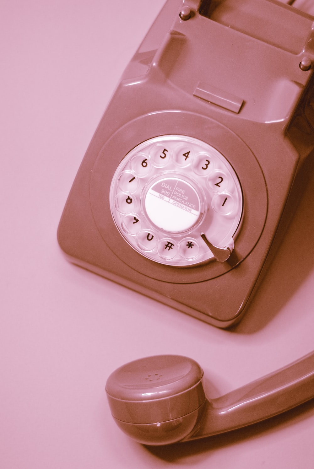 white rotary phone on pink table