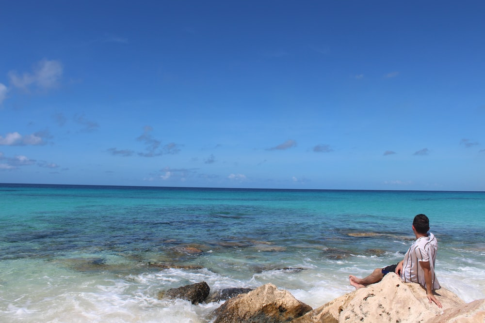 person lying on brown rock near sea under blue sky during daytime