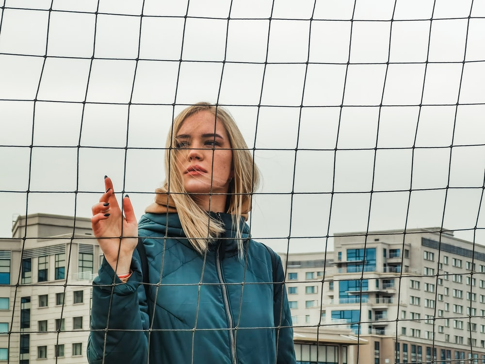 woman in blue denim jacket standing near white metal fence during daytime