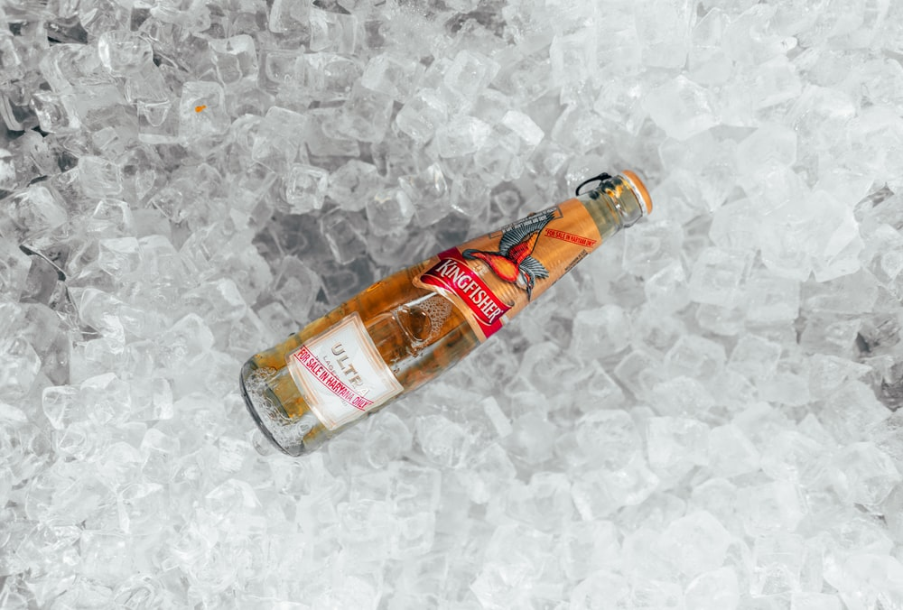 clear glass bottle on white textile
