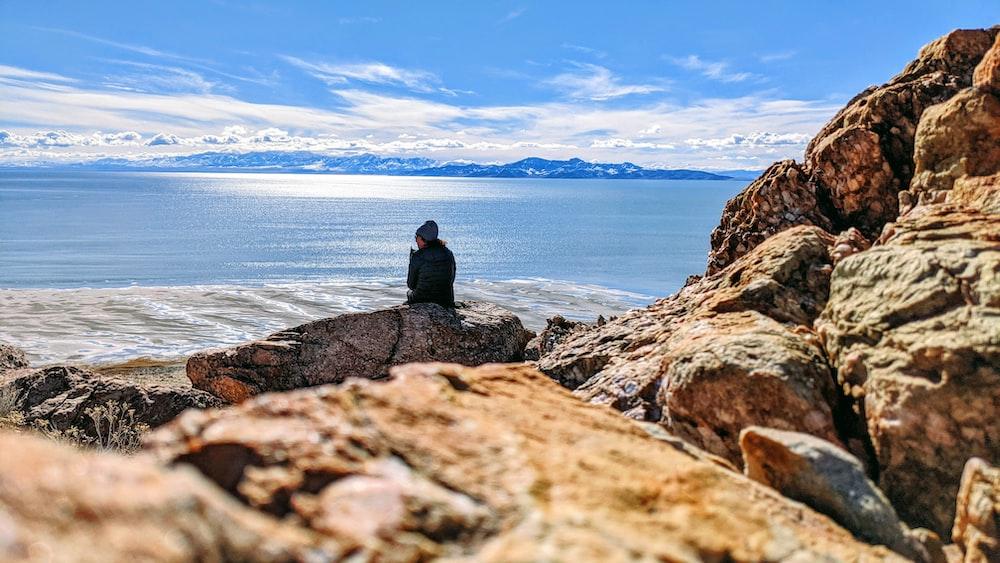 man in black jacket sitting on rock near sea during daytime