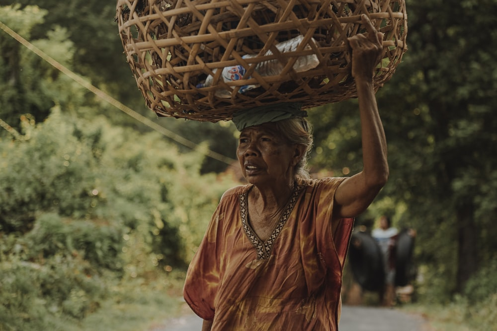 woman in orange and blue sari dress holding brown woven basket