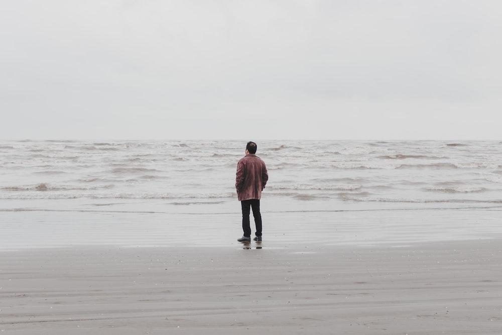 man in brown jacket walking on beach during daytime
