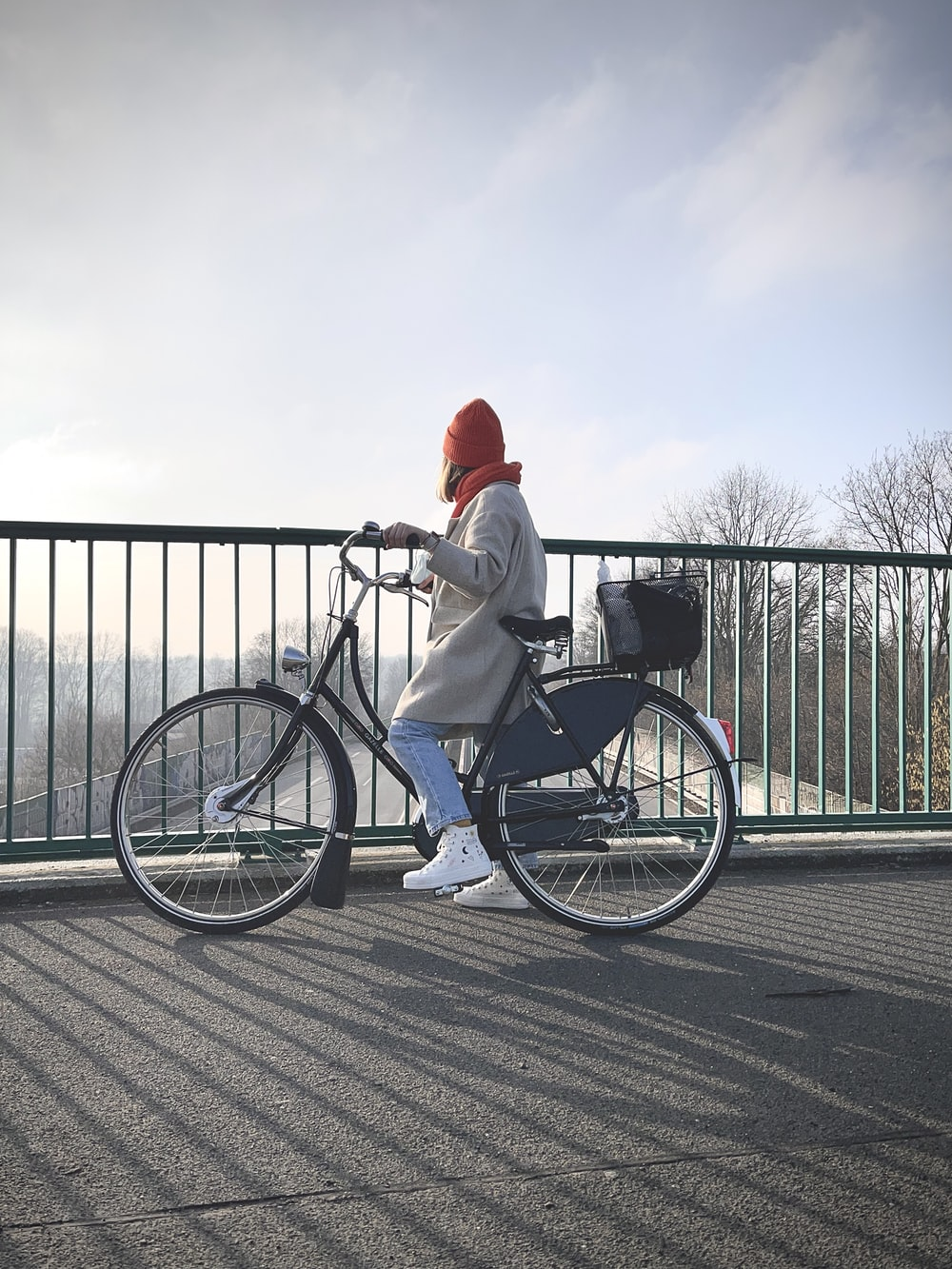 man in white long sleeve shirt and red hat riding on black bicycle
