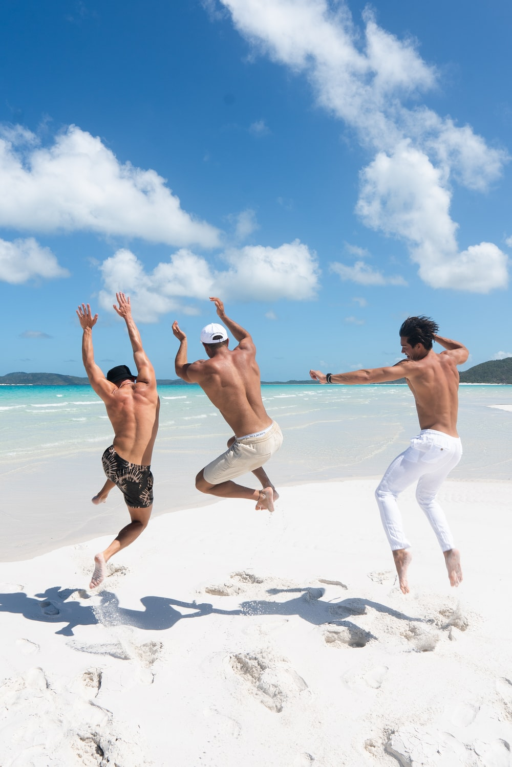 2 women in white shorts running on white sand beach during daytime