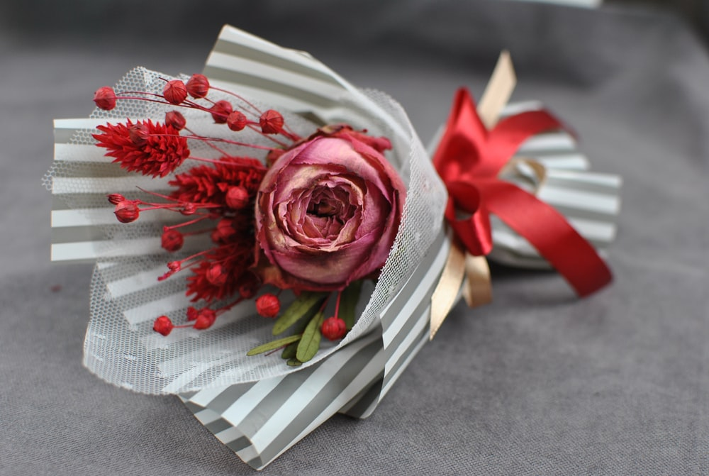 red rose on white and red gift box