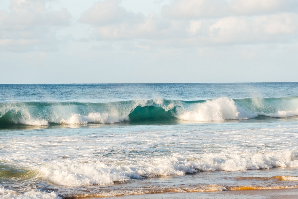 ocean waves under white clouds during daytime