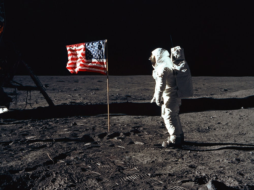 Buzz Aldrin on the moon in front of the US flag