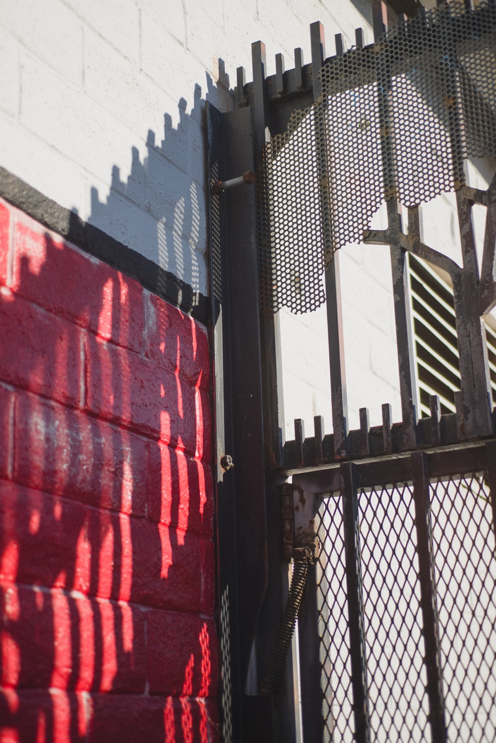 black metal fence near red and white concrete building during daytime