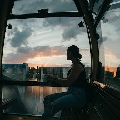 woman in black tank top sitting on window during daytime