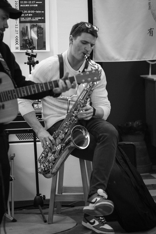 man in white crew neck t-shirt playing saxophone