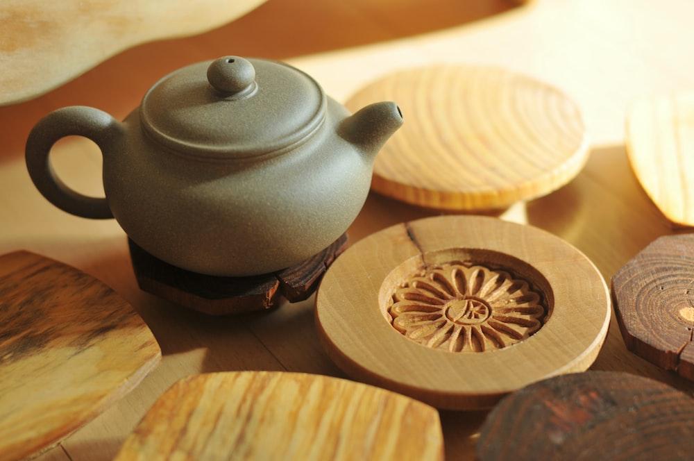 white ceramic teapot on brown wooden round table