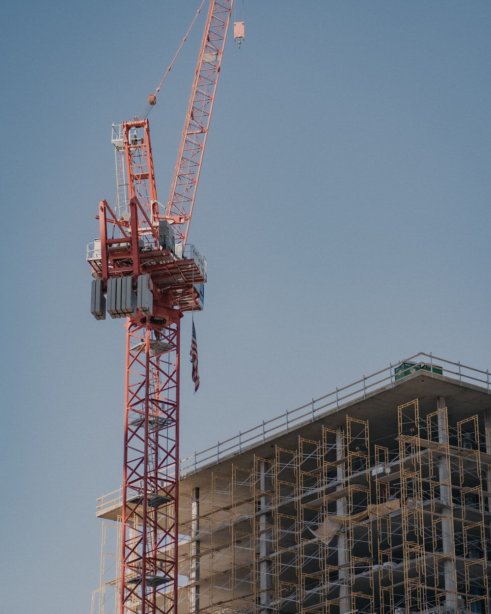 red crane near building during daytime