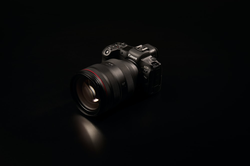 black nikon dslr camera on black surface