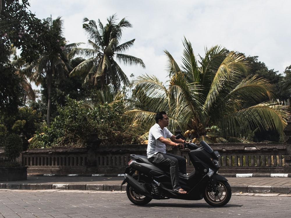man in white shirt riding black motorcycle on road during daytime