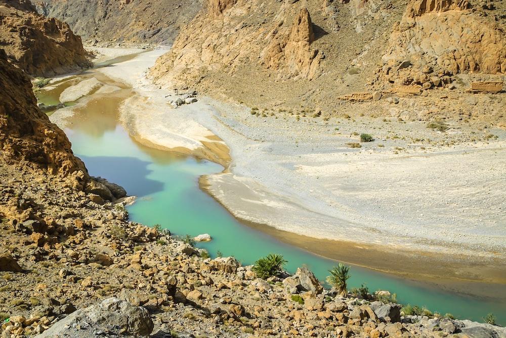 brown rocky mountain near blue lake during daytime
