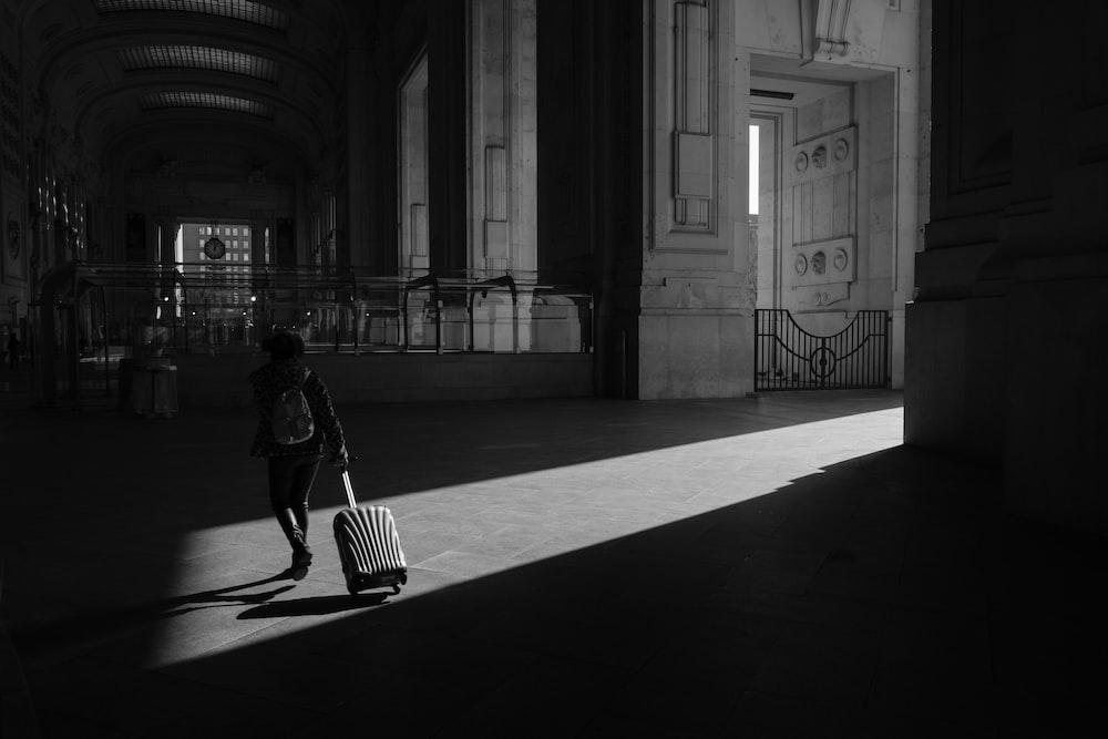 grayscale photo of woman walking on hallway