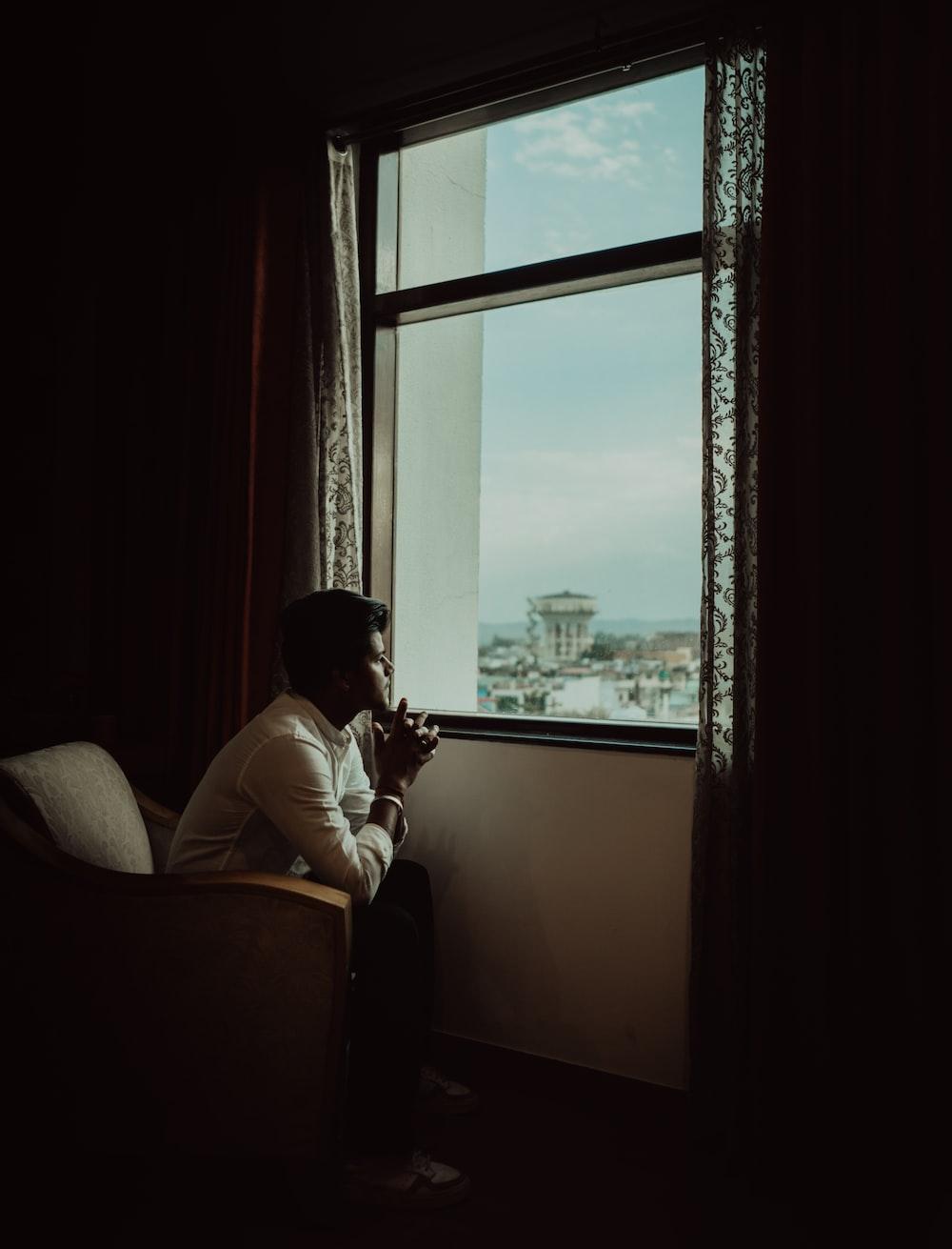 man in white dress shirt sitting on chair near window during daytime