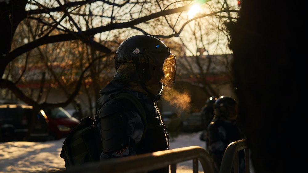 man in black jacket and black helmet sitting on bench during daytime