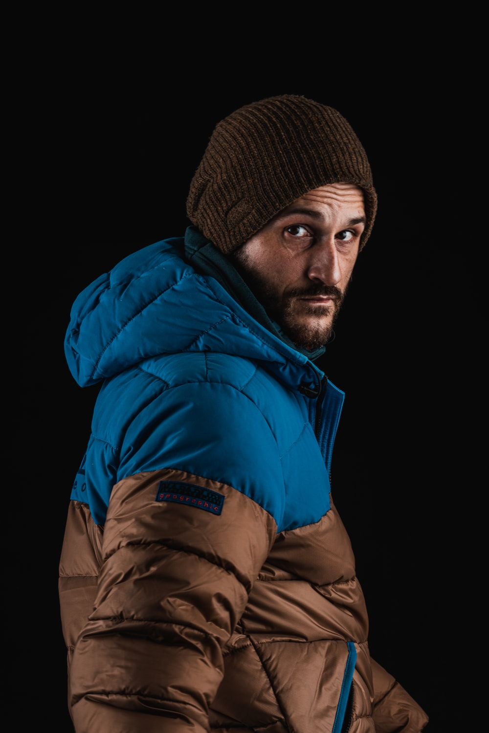 man in blue bubble jacket and brown knit cap