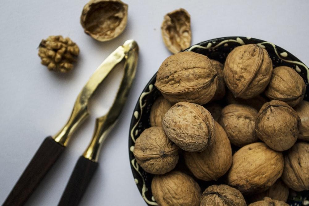 brown nuts on black ceramic bowl