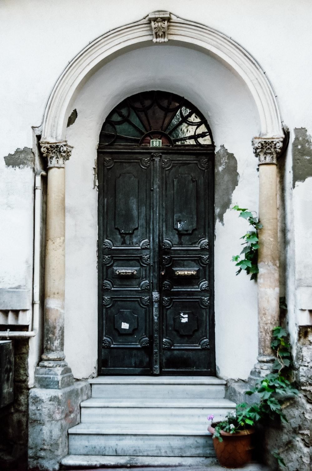 black wooden door on white concrete building