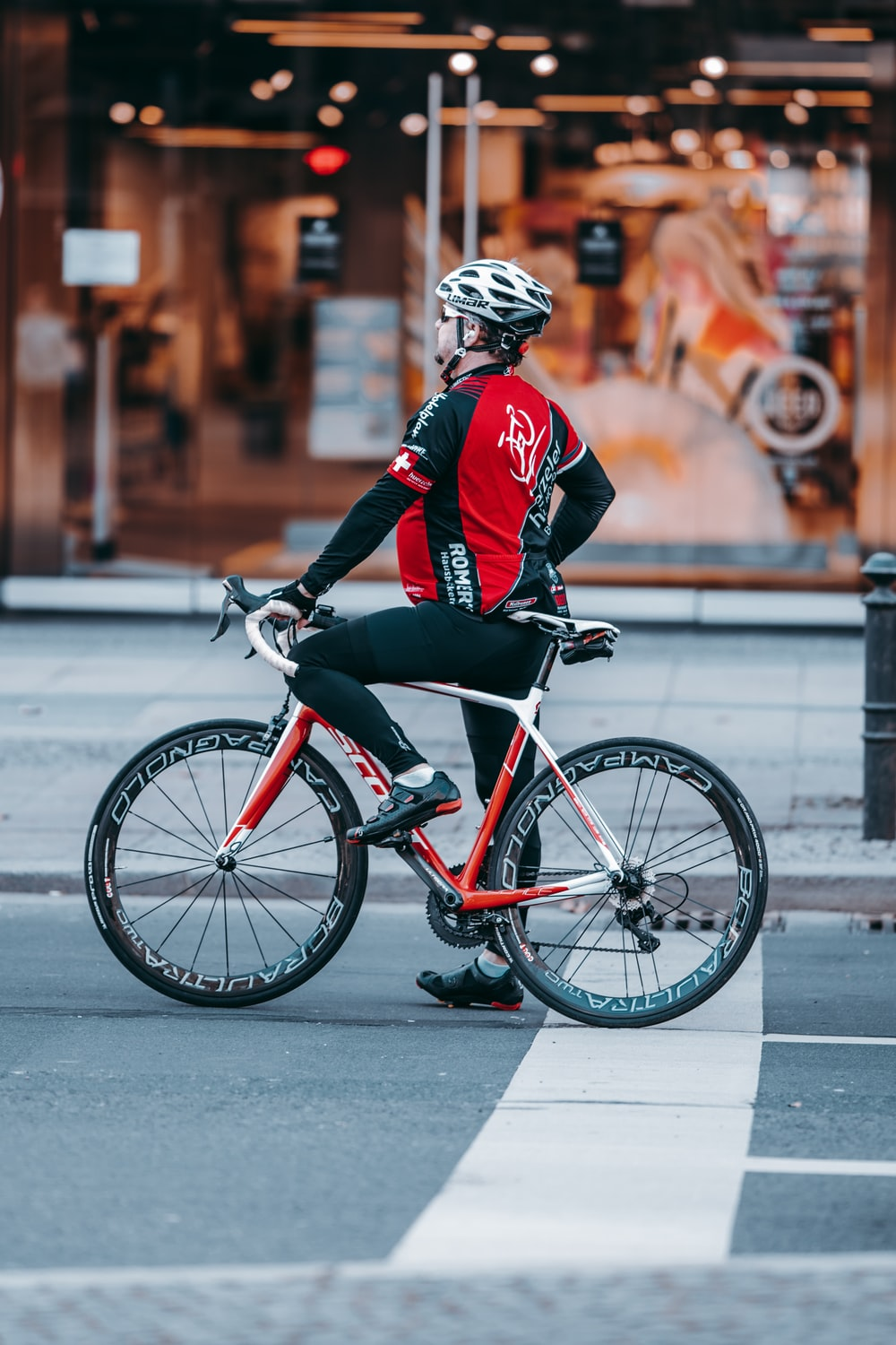 man in red and black jacket riding on bicycle