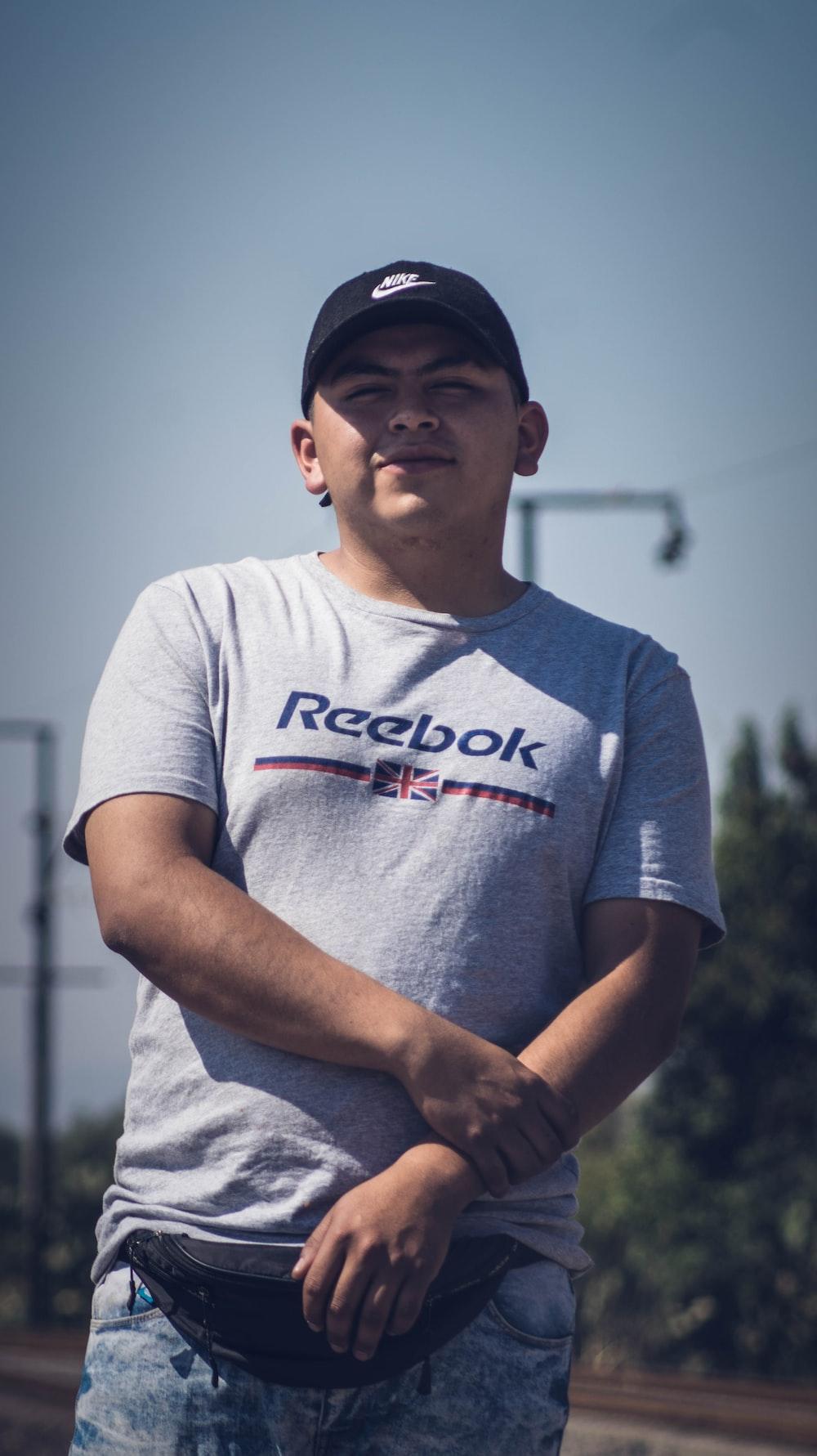 man in gray crew neck t-shirt wearing black cap