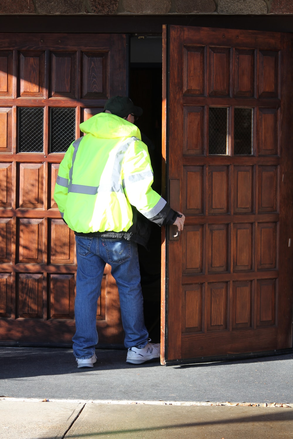 man in green and white jacket and blue denim jeans standing beside brown wooden door