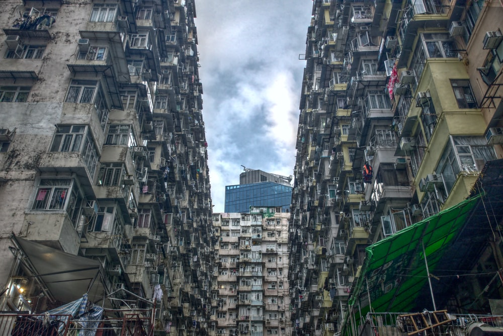 low angle photography of high rise buildings under white clouds during daytime