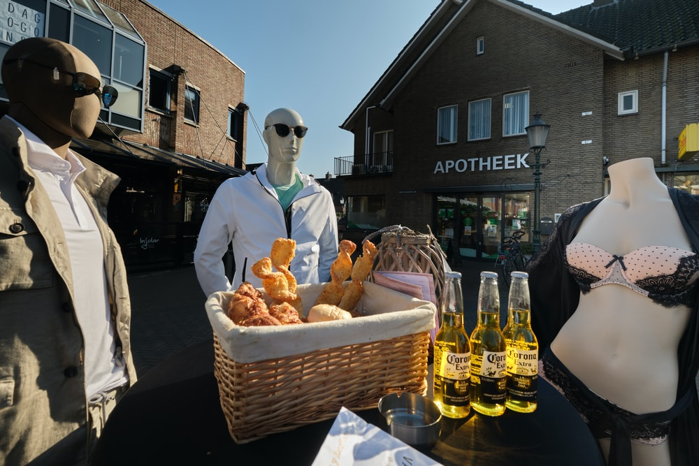 man in black suit standing beside brown wicker basket with bread