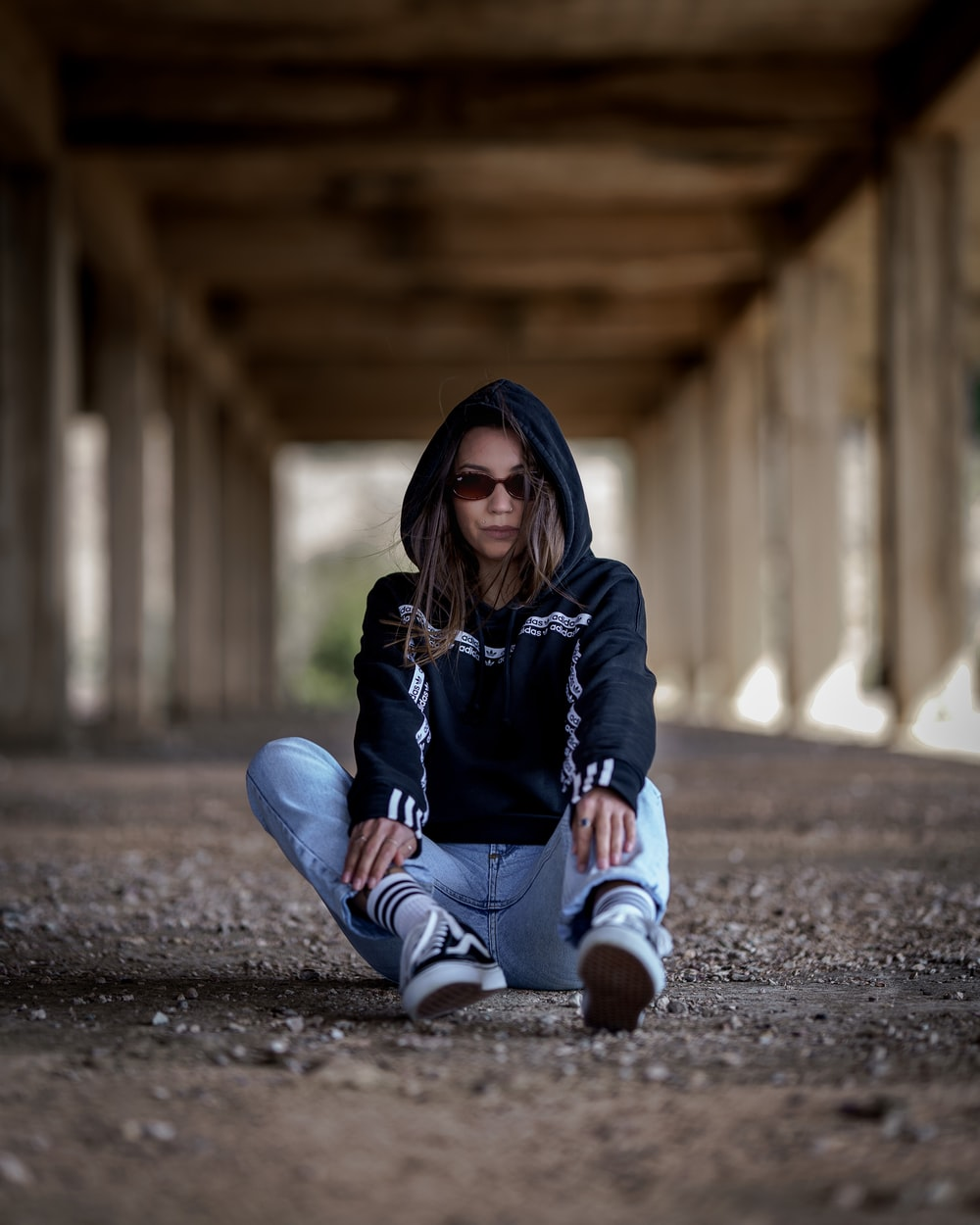 woman in black hoodie and blue denim jeans sitting on ground