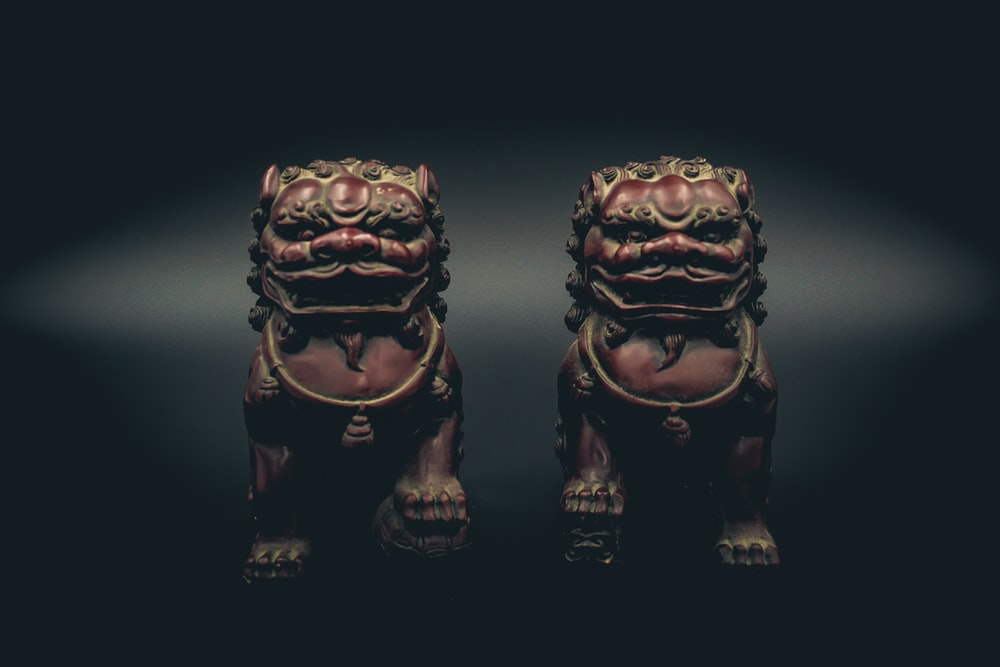 two brown ceramic figurines on black surface