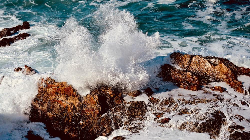 ocean waves crashing on brown rocky shore during daytime