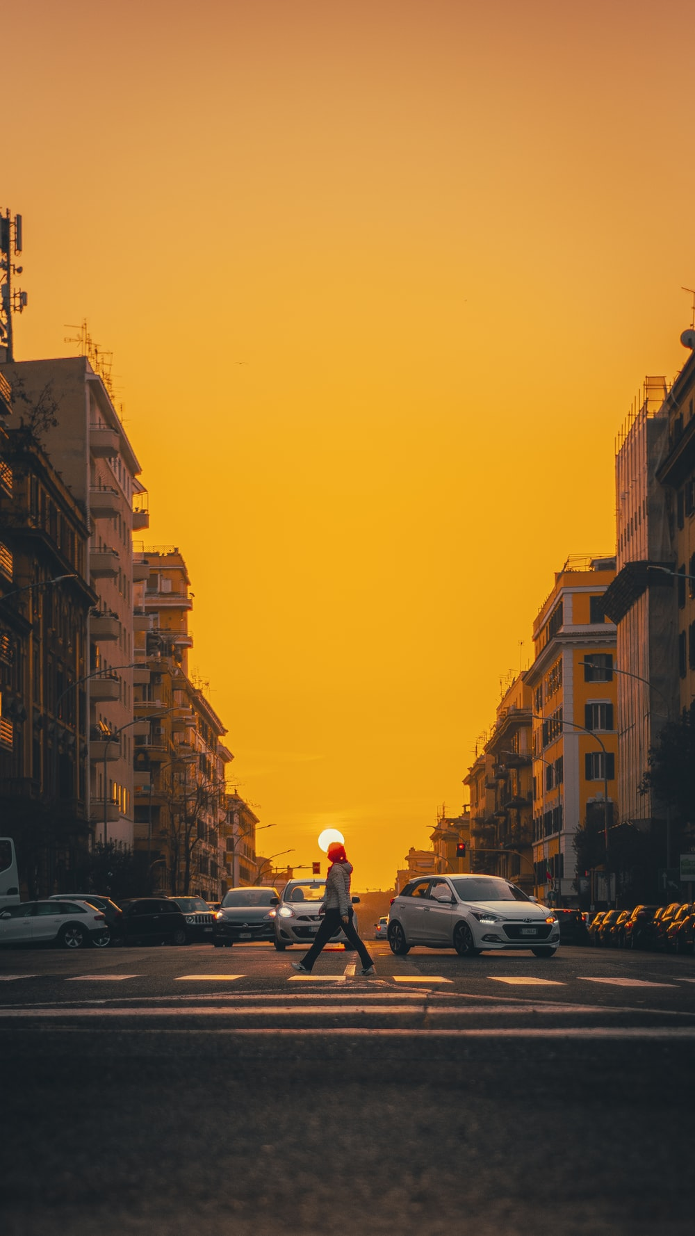 man in gray jacket and black pants walking on street during sunset
