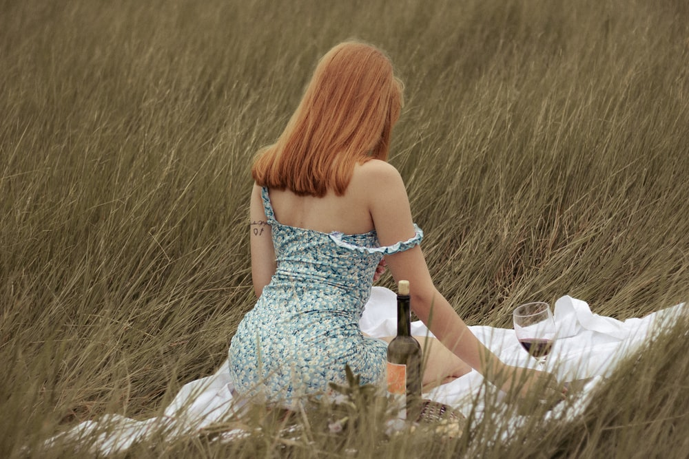 woman in white tube dress holding glass bottle