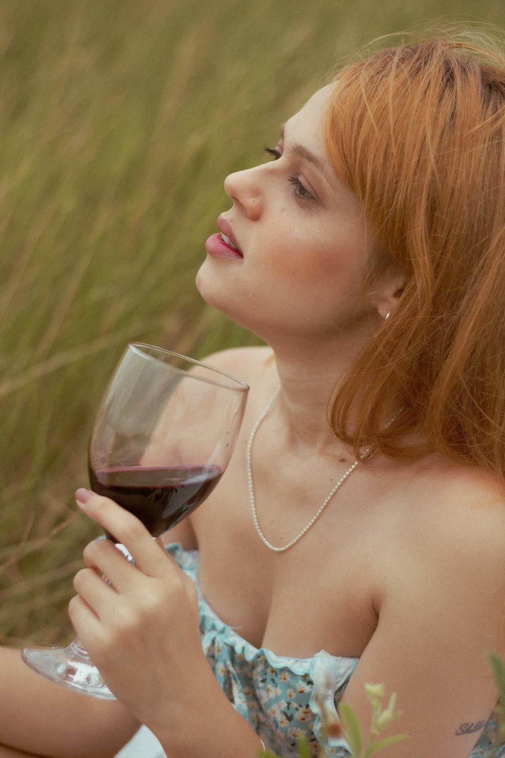 woman holding clear wine glass with red wine