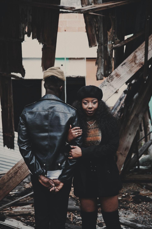 man in black suit standing beside woman in black hijab