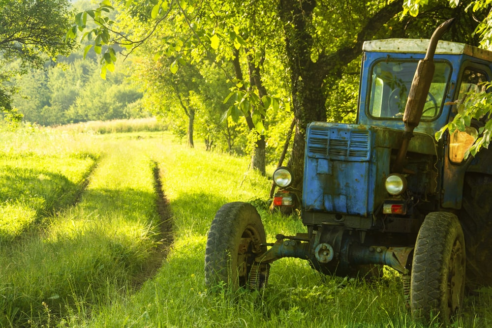 blue tractor on green grass field during daytime