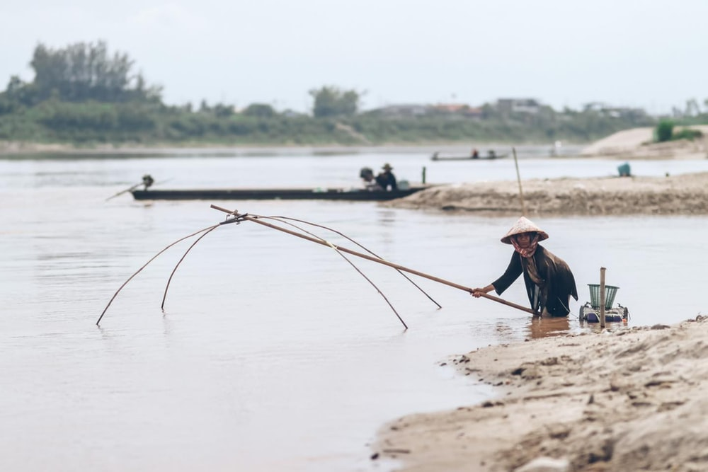 woman in blue shirt and brown hat holding brown stick near body of water during daytime