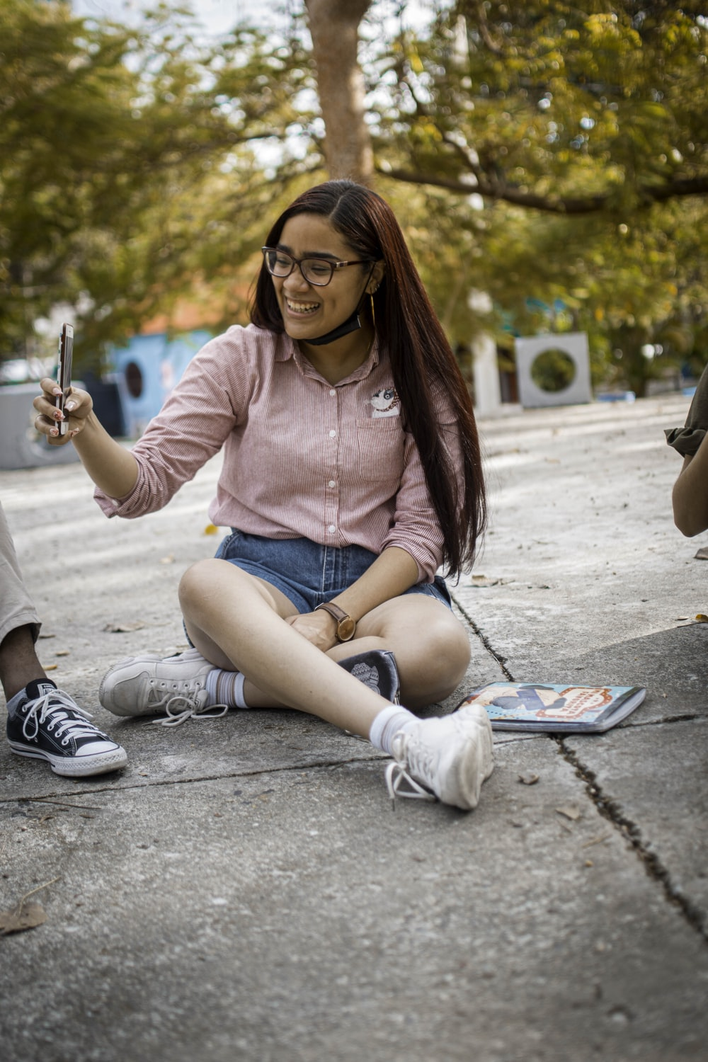 woman in pink long sleeve shirt and blue denim shorts sitting on concrete floor