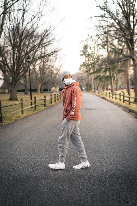 man in orange jacket and white pants walking on gray asphalt road during daytime