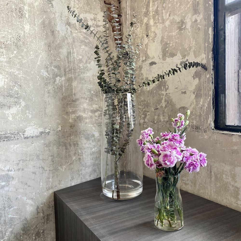 purple flowers in clear glass vase