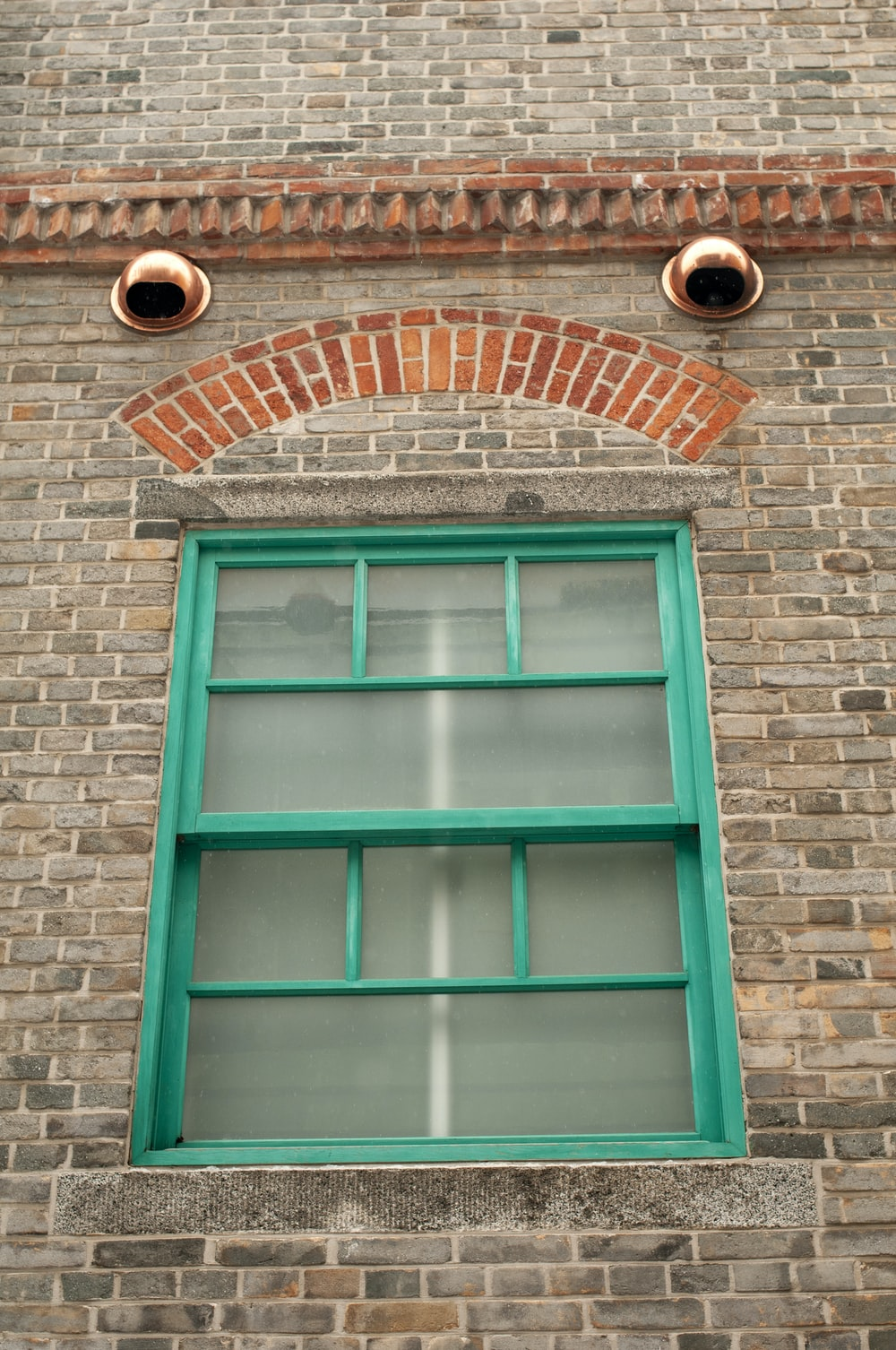 green wooden window frame on brown brick wall