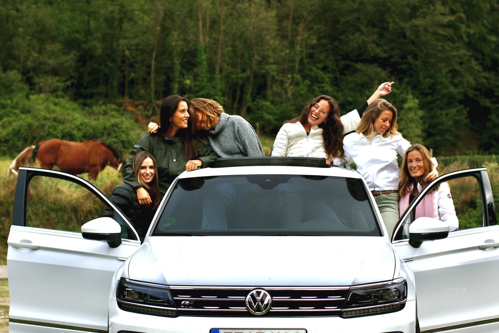 group of people standing beside white car during daytime