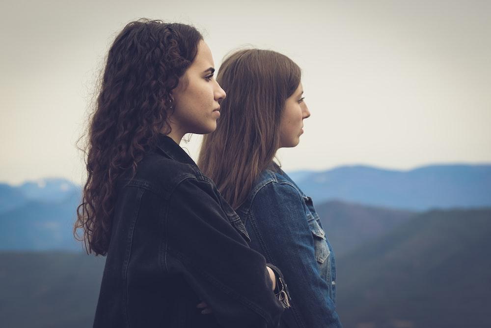 woman in black leather jacket beside woman in blue denim jacket