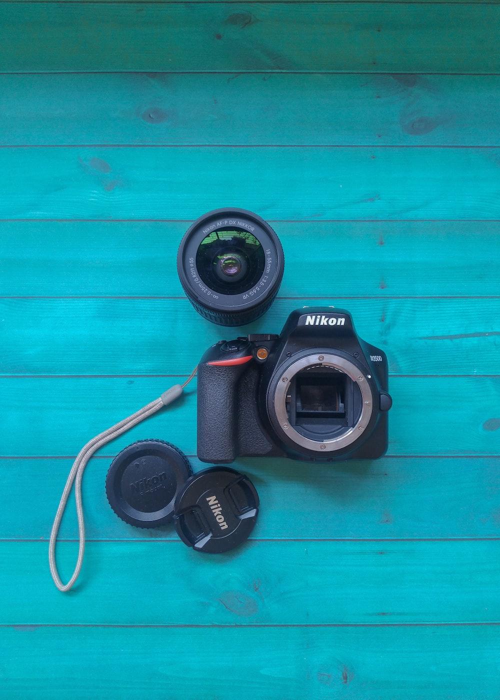 black nikon dslr camera on blue wooden surface