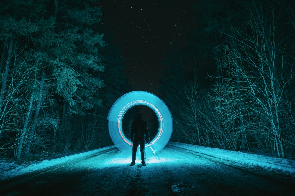 person in black jacket standing on snow covered ground during night time
